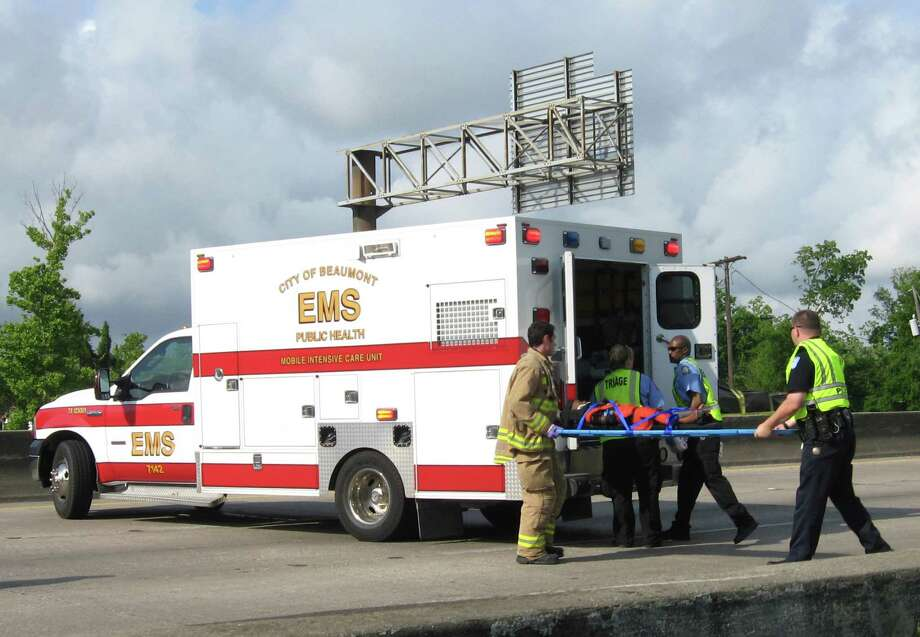 Beaumont EMS workers carry an accident victim to a waiting ambulance after a wreck on Interstate 10 in April. A ride to the hospital can cost around $800.  Enterprise file photo Photo: Dan Wallach