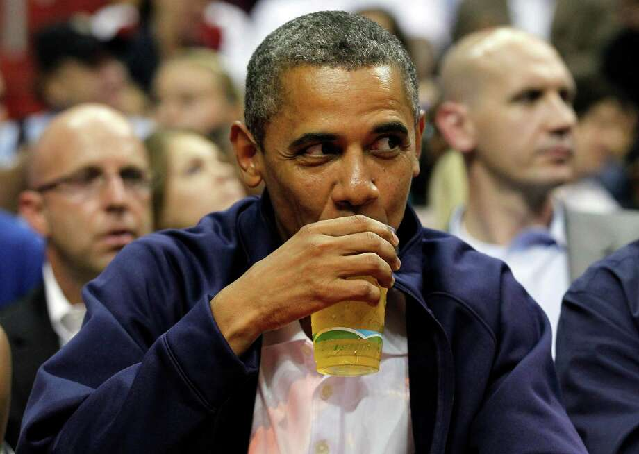 President Barack Obama sips his beer as he watches Team USA and Brazil during the first half of an Olympic men's exhibition basketball game, Monday, July 16, 2012, in Washington. (AP Photo/Alex Brandon) Photo: Alex Brandon, Associated Press / AP