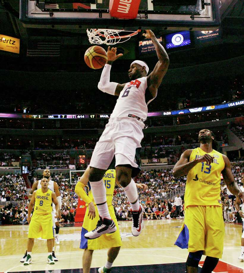 Team USA forward LeBron James (6) dunks the ball with Brazil center Maybyner Rodney Hilario, right, during the first half of an Olympic men's exhibition basketball game, Monday, July 16, 2012, in Washington. (AP Photo/Alex Brandon) Photo: Alex Brandon, Associated Press / AP