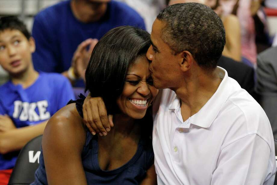 """President Barack Obama kisses the head of first lady Michelle Obama, left, after kissing her for """"Kiss Cam"""" in the second half while attending the Olympic men's exhibition basketball game between Team USA and Brazil, Monday, July 16, 2012, in Washington. Team USA won 80-69. (AP Photo/Alex Brandon) Photo: Alex Brandon, Associated Press / AP"""