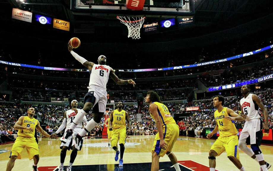 Team USA forward LeBron James goes up for a dunk in front of Brazil forward Anderson Varejao (11) during the first half of an Olympic men's exhibition basketball game, Monday, July 16, 2012, in Washington. USA won 80-69. (AP Photo/Alex Brandon) Photo: Alex Brandon, Associated Press / AP