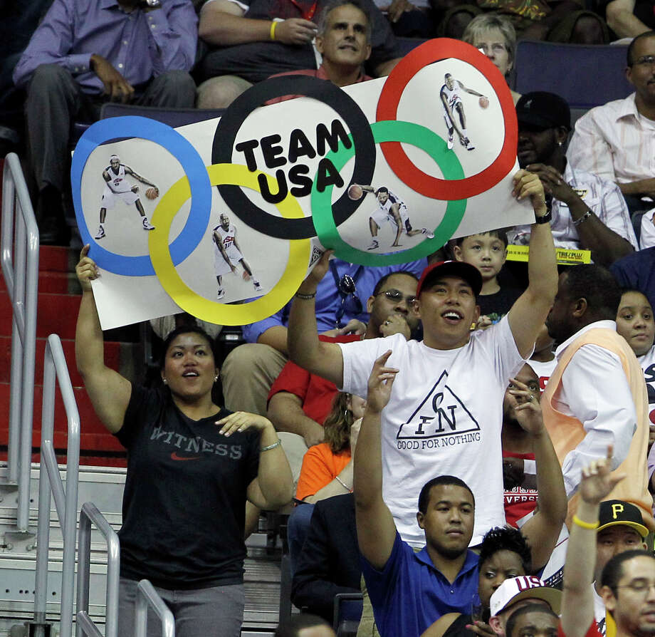 Fans hold an Olympic Rings sign for Team USA during the first half of an Olympic men's exhibition basketball game against Brazil, Monday, July 16, 2012, in Washington. (AP Photo/Alex Brandon) Photo: Alex Brandon, Associated Press / AP
