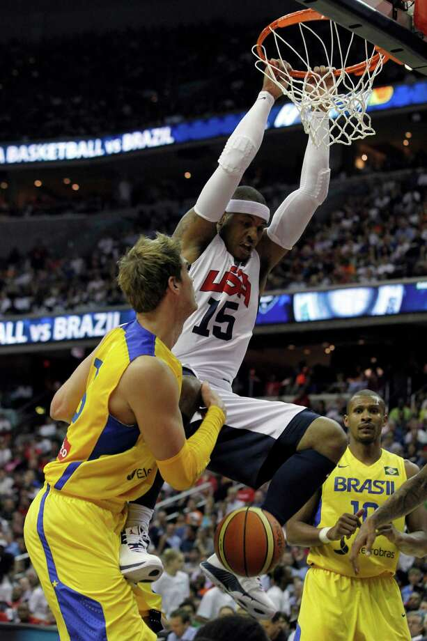 Team USA's Carmelo Anthony (15) dunks the ball in front of Brazil's Raul Togni Neto, left, and Leandro Mateus Barbosa during the first half of an Olympic men's exhibition basketball game, Monday, July 16, 2012, in Washington. Team USA won 80-69. (AP Photo/Alex Brandon) Photo: Alex Brandon, Associated Press / AP