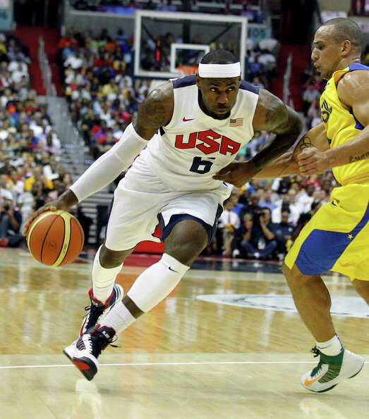 Team USA forward LeBron James works to get past team Brazil guard Alex Ribeiro Garcia during the fir