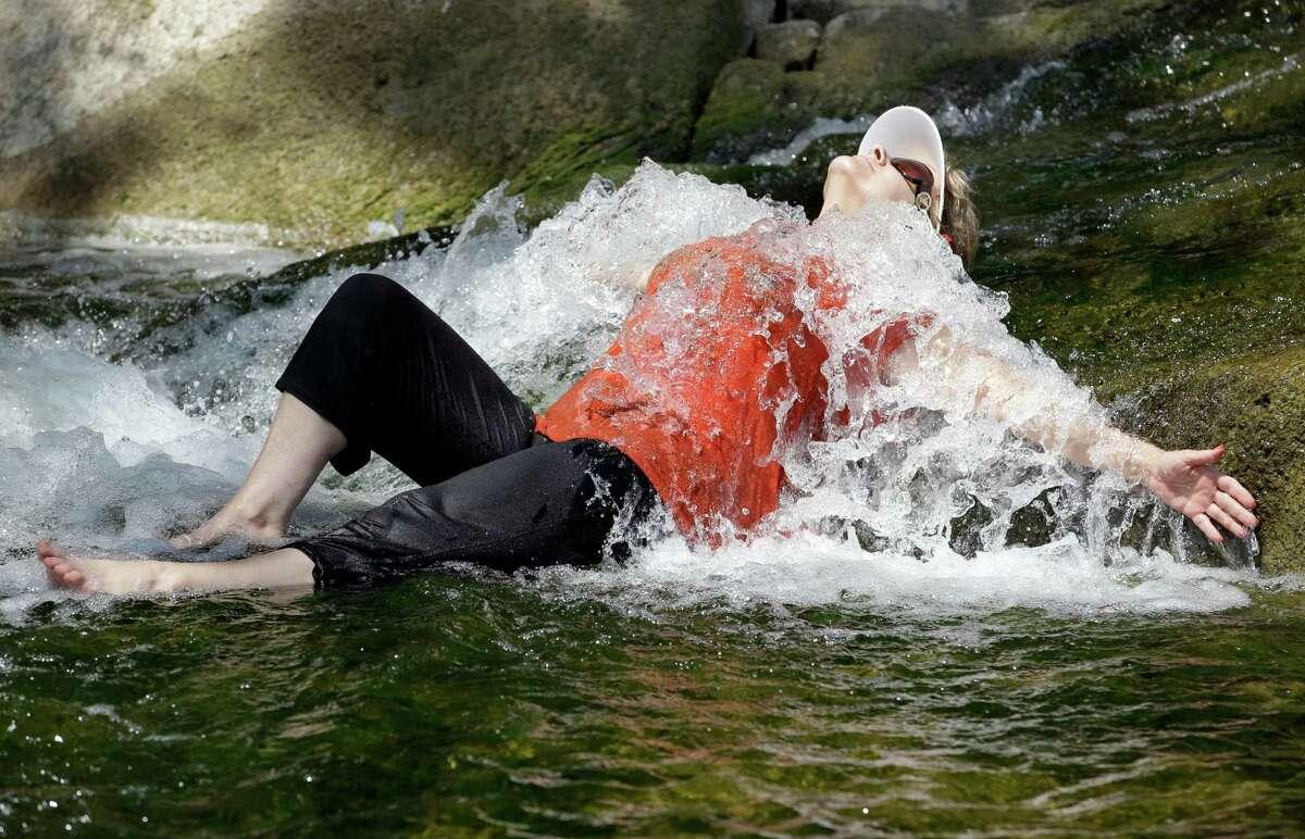 Karen VanDeVoorde cools off in a waterfall during the hot summer weather in Indian Falls, N.Y., Monday, July 16, 2012.