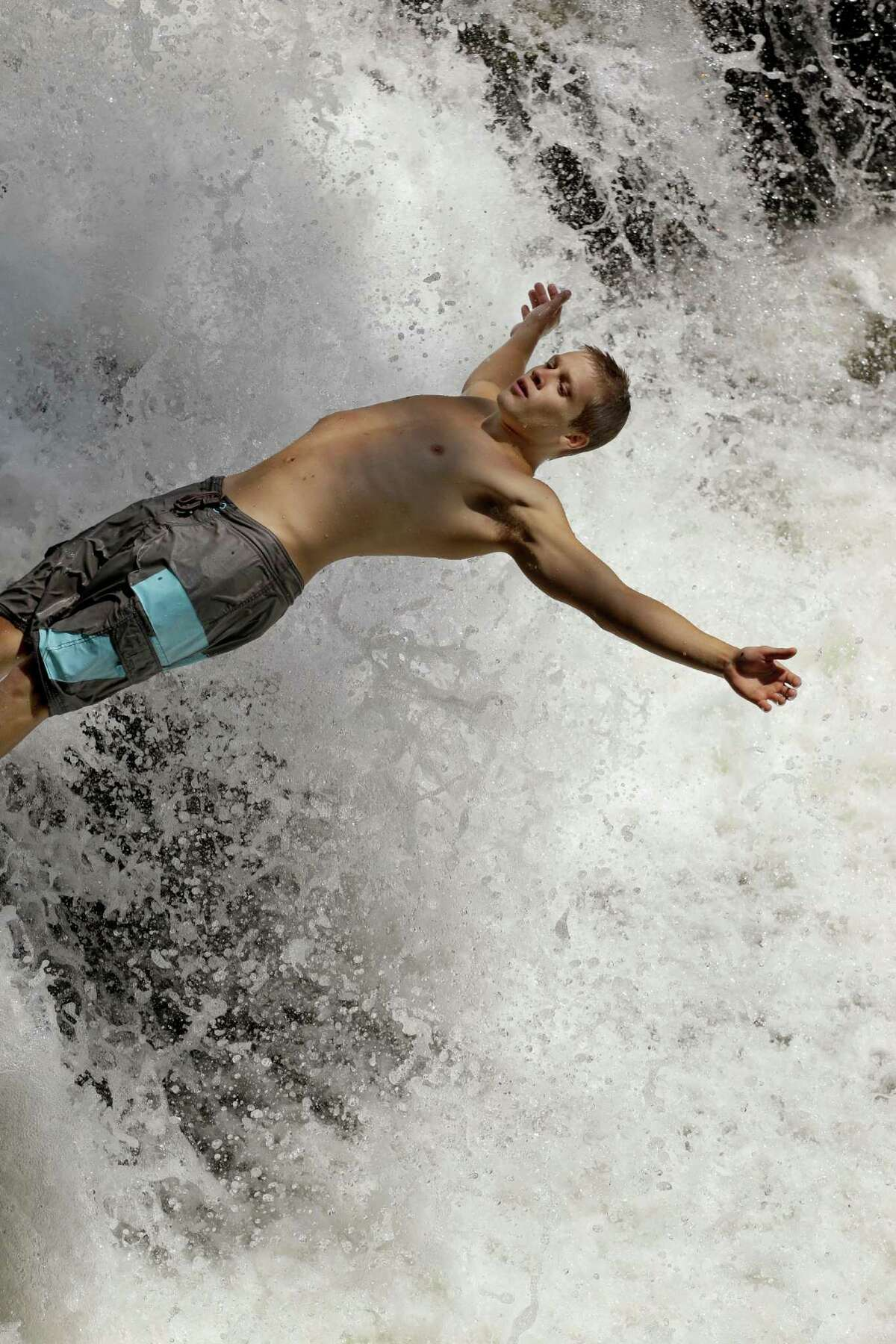 Jamie Scherer jumps off a waterfall during the hot summer weather in Indian Falls, N.Y., Monday, July 16, 2012.