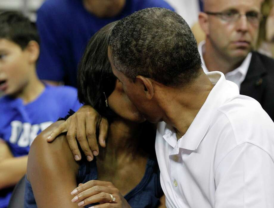 President Barack Obama, right, kisses first lady Michelle Obama for the 'Kiss Cam' while attending the Olympic men's exhibition basketball game between Team USA and Brazil, Monday, July 16, 2012, in Washington. Team USA won 80-69. (AP Photo/Alex Brandon) Photo: Alex Brandon