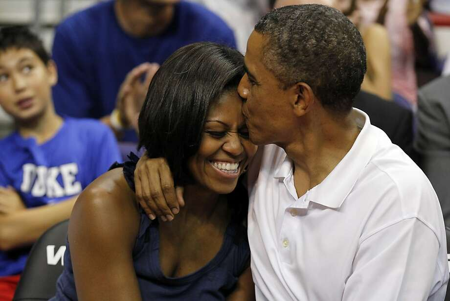 """President Barack Obama kisses the head of first lady Michelle Obama, left, after kissing her for """"Kiss Cam"""" in the second half while attending the Olympic men's exhibition basketball game between Team USA and Brazil, Monday, July 16, 2012, in Washington. Team USA won 80-69. Photo: Alex Brandon, Associated Press"""