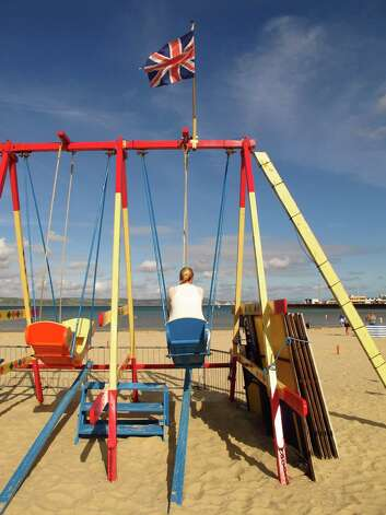 A British flag flies over a swing set on Weymouth Bay beach, which is about to get a whole lot busier as Olympic crowds invade this scenic Georgian town.   The area will be the site of 2012 Olympic sailing events. Photo: Amy Laughinghouse, For The Express-News