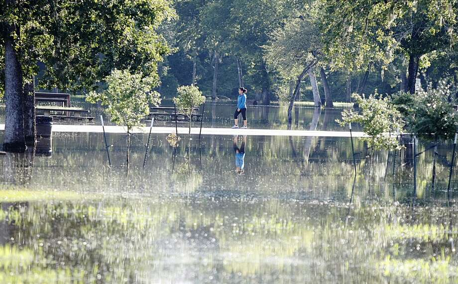 A runner has to turn around after approaching an impassable road at Bear Creek Pioneer Park on Tuesday morning. Photo: Nick De La Torre, Houston Chronicle