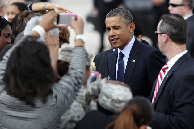 U.S. President Barack Obama greets guests upon his arrival at San Antonio International Airport, Tuesday, July 17, 2012. Obama is attending two fundraising events, one at the Convention Center and another one at a private residence in the Dominion. Photo: Jerry Lara / © 2012 San Antonio Express-News