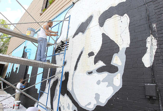Joshua Bennett of MOCA works on a mural of Sam Houston on Washington near Sawyer on Tuesday, July 17, 2012. Photo: Nick De La Torre / Chronicle