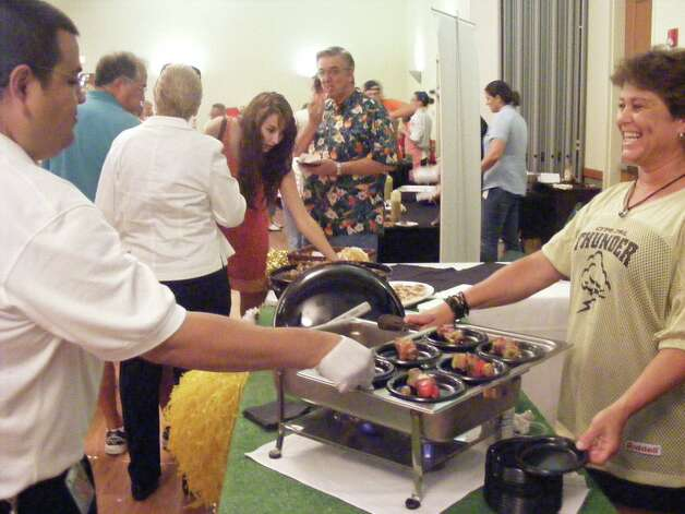 "An attendee to the 2011 Schertz Chamber of Commerce ""Taste"" enjoys a shish-kabob from one of the two dozen participating vendors. This year's ""Taste: Around The World"" is set for 5-8 p.m. July 26 at the Schertz Civic Center. Photo: NE Herald File Photo"