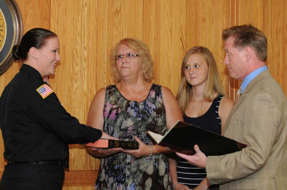 Jennifer L. Shevy, Watervliet native and Iraq war veteran, is sworn in by Mayor Michael Manning as only the second woman on the Watervliet Police force at Watervliet City Hall on Tuesday, July 17, 2012, in Watervliet, N.Y. Her mother, Debbie Shevy, holds the Bible and her sister Tabitha, 16, looks on. (Lori Van Buren / Times Union) Photo: Lori Van Buren