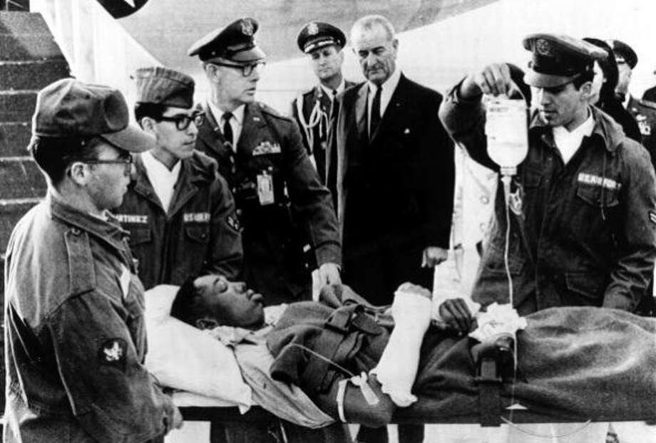 Lyndon B. Johnson looks on as a U.S. serviceman wounded in Vietnam is gently lifted from a plane in San Antonio, Dec. 24, 1966.