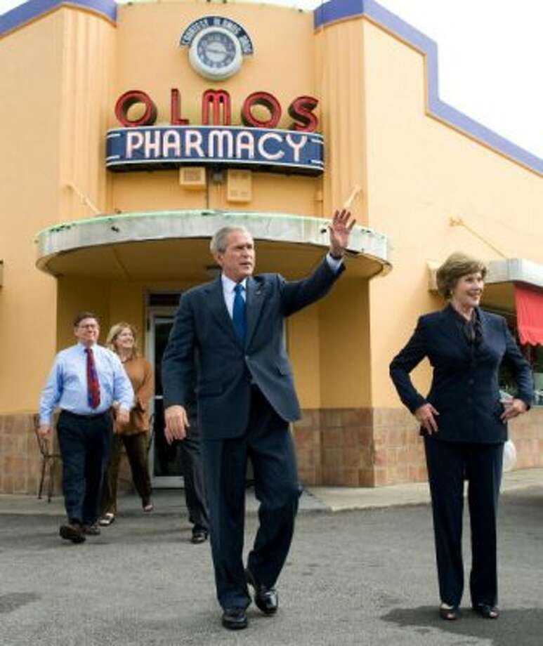 Prior to a speech regarding the economy, then U.S. President George W. Bush waved alongside his wife Laura Bush to local small business leaders in San Antonio, Texas, October 6, 2008. Bush had traveled to attend a Republican fundraiser in the city, and made an unannounced visit to the Pharmacy. (Saul Loeb / AFP/Getty Images)