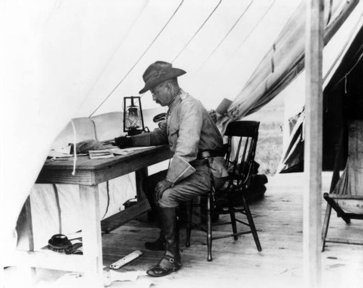 Theodore Roosevelt working at a desk inside his tent in San Antonio, Texas, during the training of the Rough Riders in 1898.