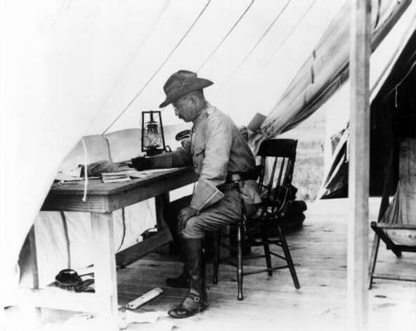 Theodore Roosevelt working at a desk inside his tent in San Antonio, Texas, during the training of the Rough Riders in 1898.  (Express-News file photo)