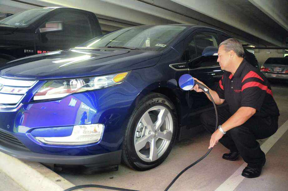 Rick Reina, of The Woodlands, plugs in the electric charging cord to recharge his Chevrolet Volt at the car charging station in the Market Street parking garage. The Blink charging station serves all vehicles with the J1772 connector, commonly used on all electric cars. Photo: David Hopper / freelance