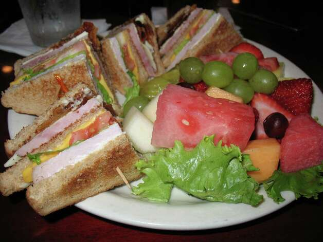 A club sandwich is served with fresh fruit at Raffles. Photo: Jennifer McInnis, San Antonio Express-News
