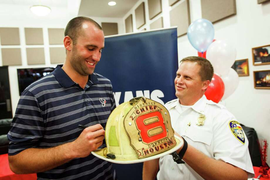 Houston Texans QB Matt Schaub, left, signs an autograph on a helmet for District Chief Eric Hutzley during a visit to Fire Station No. 8 to  present an autographed No. 8 football jersey to the firefighters,  Tuesday, July 17, 2012, in Houston. Photo: Michael Paulsen, Houston Chronicle / © 2012 Houston Chronicle