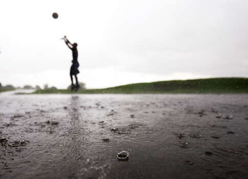 Quincy Rivera plays basketball in the rain at Herman Brown Park on the east side. Photo: .