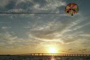 Parasailers soar over Laguna Madre Bay and the Queen Isabella Causeway connecting Port Isabel and South Padre Island. July 7, 2012