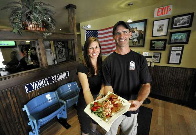 Anita Susco and her cousin, establishment owner Larry Debany, hold a plate featuring lobster roll at Fifty Coins Restaurant in Ridgefield Friday, July 6, 2012. Photo: Michael Duffy / The News-Times