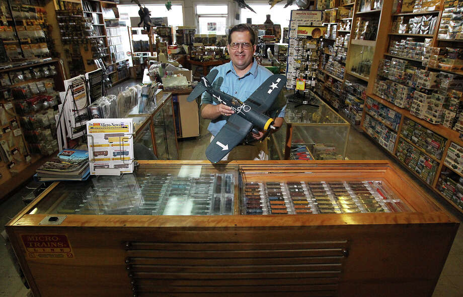 Dibble's Hobbies owner Jeff Chladek stands in front of a unique TraySure case made by previous owners Raymond Johnson and Lynn Hurta. The case was customized with sliding shelves to showcase the store's collection of miniature model trains.