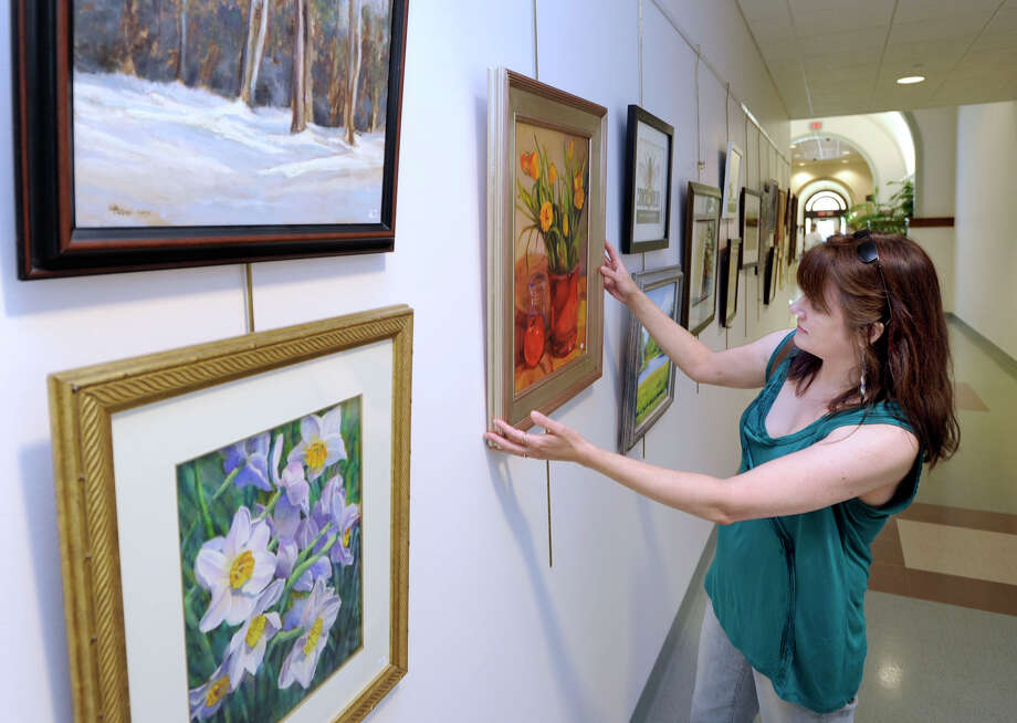 """Lisa Greto, of Sandy Hook, straighten's her oil painting, """"Theresa's Tulips,"""" which is hanging in an artshow at the Newtown Municipal Center, Tuesday, July 17, 2012. Photo: Carol Kaliff"""