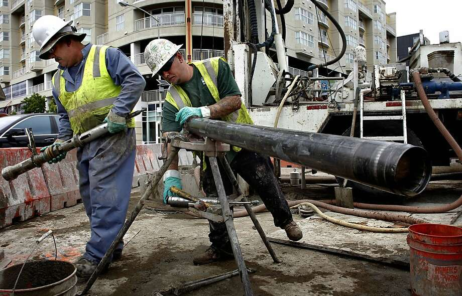 Roland Medina, (left) and Will Stewart take core samples to determine the composition of the earth before the tunnel digging begins, on the Central Subway project through downtown San Francisco, Calif., along Fourth Street, between Harrison and Bryant Streets, on Friday July 13, 2012. Photo: Michael Macor, The Chronicle