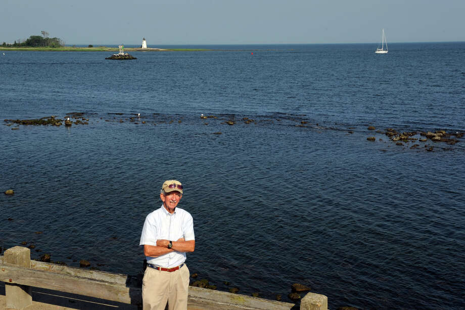 """Former Town of Fairfield Historian Bill Lee stands at St. Mary's by the Sea, in Bridgeport, Conn., where a man made formation of rocks can be seen at low tide. Lee believes the formation to be the remains of a """"Rebel Fort"""", depicted on a 1779 British map, and that the fort protected Black Rock Harbor against British invasion. Photo: Ned Gerard"""