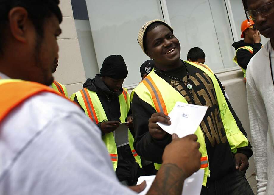Jay Davis (center), 19,  collects his first paycheck from team leader Robert Taito (left), 25 as he and others in the second 5 week-session of the San Francisco Department of Public Works program receive their checks after landscaping a median on Geary Boulevard on Thursday, July 12, 2012 in San Francisco, Calif. Photo: Lea Suzuki, The Chronicle