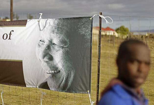A man passes a banner showing former South African president Nelson Mandela in Qunu, South Africa, Tuesday, July 17, 2012. South African's will celebrate former president Nelson Mandela's birthday tomorrow. (AP Photo/Schalk van Zuydam) Photo: Schalk Van Zuydam, Associated Press
