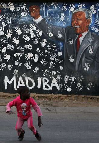 A young girl plays in front a mural depicting former South African President Nelson Mandela at the Alexandra township in Johannesburg, South Africa, Tuesday, July 17, 2012, to honor Mandela's 94th birthday which was celebrated Wednesday, July 18, 2012. (AP Photo/Themba Hadebe) Photo: Themba Hadebe, Associated Press