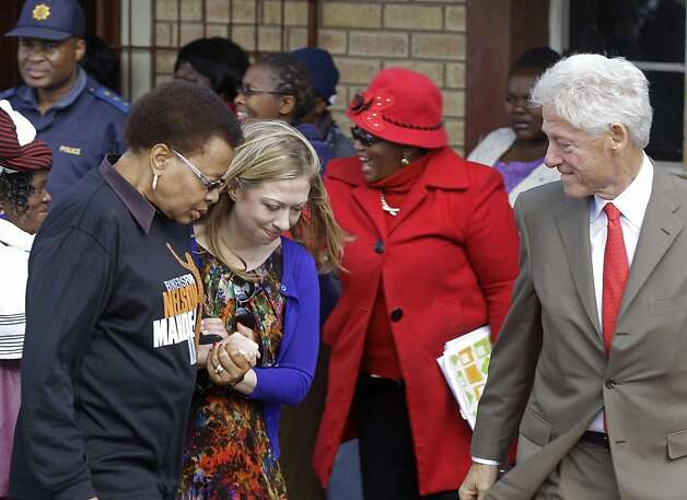 South Africa's Graça Machel, left, walks with Chelsea Clinton, second left, and her dad former American president Bill Clinton, right,  as they arrive at a party to celebrate former South African president Nelson Mandela birthday in Qunu, South Africa, Tuesday, July 17, 2012. South African's will celebrate former president Nelson Mandela's birthday tomorrow.  (AP Photo/Schalk van Zuydam) Photo: Schalk Van Zuydam, Associated Press