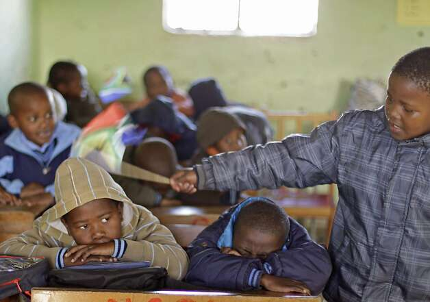 A child keeps control over fellow students by tapping them with a South African flag as they were instructed nap at the No-Moscow school before celebrations for former South African president Nelson Mandela in Qunu, South Africa, Tuesday, July 17, 2012. South African's will celebrate former president Nelson Mandela's birthday tomorrow. (AP Photo/Schalk van Zuydam) Photo: Schalk Van Zuydam, Associated Press