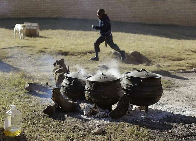A child runs past food being cooked at the No-Moscow school for celebrations for former South African president Nelson Mandela in Qunu, South Africa, Tuesday, July 17, 2012. South African's will celebrate former president Nelson Mandela's birthday tomorrow. (AP Photo/Schalk van Zuydam) Photo: Schalk Van Zuydam, Associated Press