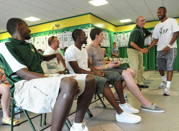 From left, former Siena basketball players Prosper Karangwa, Ronald Moore, Ryan Rossiter and Siena head coach Mitch Buonaguro congratulates former Siena basketball player Kenny Hasbrouck for being picked second in the draft pick at the Siena Legends news conference and draft on Tuesday, July 17, 2012 in Loudonville, N.Y.  (Lori Van Buren / Times Union) Photo: Lori Van Buren