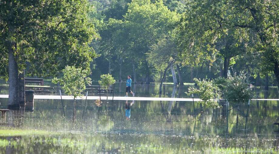 The high water that forced this Bear Creek park jogger to turn back Tuesday soon could be the breeding ground for mosquitoes. Photo: Nick De La Torre / © 2012  Houston Chronicle