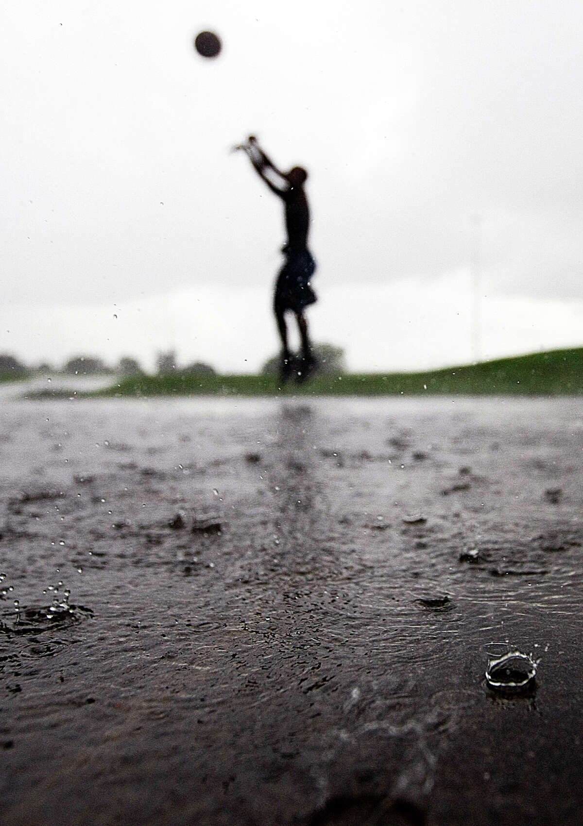 """Quincy Rivera, 13, plays basketball as rain fell in Herman Brown Park Tuesday, July 17, 2012, on the east side of Houston. in it was """"pretty fun and different."""" ( Johnny Hanson / Houston Chronicle )"""