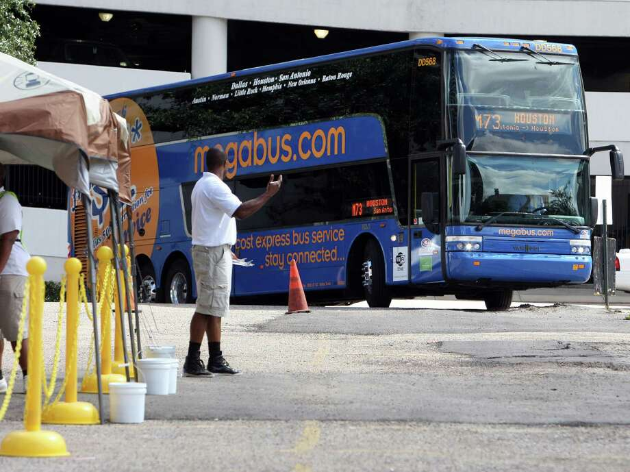 Megabus ground staff Richard Hutton signals a Megabus as it arrives at the pickup-departure area at Travis and Clay streets, Megabus is a low-cost inter-city bus company that has recently started service in Texas Tuesday, July 17, 2012, in Houston. ( James Nielsen / Chronicle ) Photo: James Nielsen / © Houston Chronicle 2012