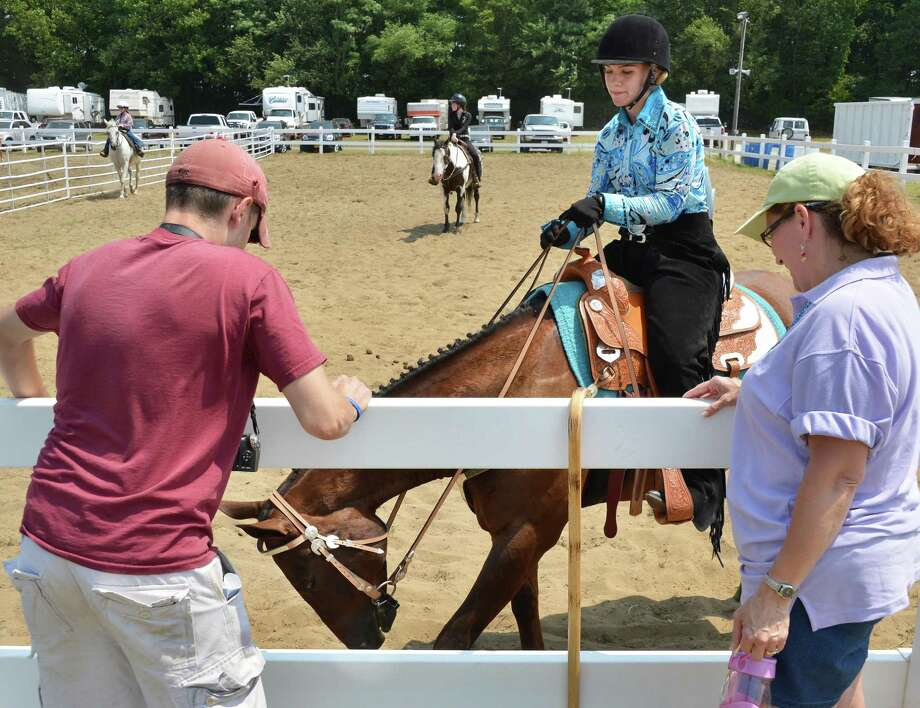 "Rachel Trojan, 18, of Scotia and her horse ""Mack"" await the start of the 4H horse show with fans, boyfriend Matt Rickard, left, and her mother Carolyn Trojan at the 171st Saratoga County Fair in Ballston Spa Tuesday July 17, 2012.   (John Carl D'Annibale / Times Union) Photo: John Carl D'Annibale / 00018353A"