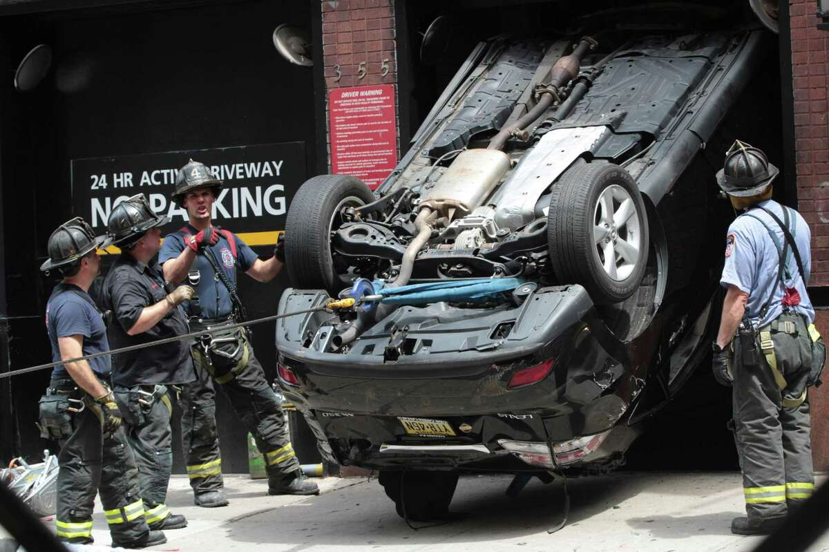 Firefighters work to extricate a car that fell down an elevator shaft at a garage in Midtown, Tuesday, July 17, 2012 in New York. Temperatures are expected to reach into the high 90s Tuesday in the New York metropolitan area. (AP Photo/Mary Altaffer)