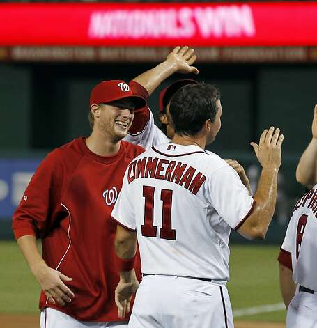 Washington Nationals starting pitcher Ross Detwiler, left, smiles at Ryan Zimmerman (11) after Zimmerman scored the winning run during the 10th inning of a baseball game against the New York Mets on Tuesday, July 17, 2012, in Washington. The Nationals won 5-4. (AP Photo/Alex Brandon) Photo: Alex Brandon, Associated Press