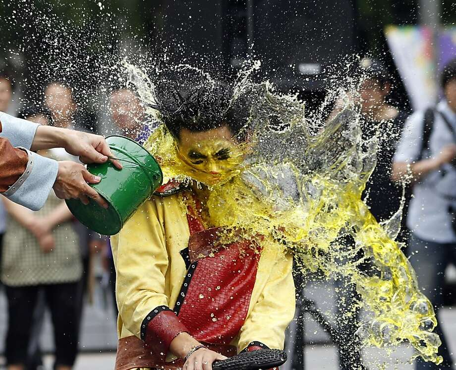 Participants splash colored water each other during a water festival in Seoul, South Korea, Tuesday, July 17, 2012. The event promotes tourism of local county offices ahead of summer vacation season. (AP Photo/Lee Jin-man) Photo: Lee Jin-man, Associated Press