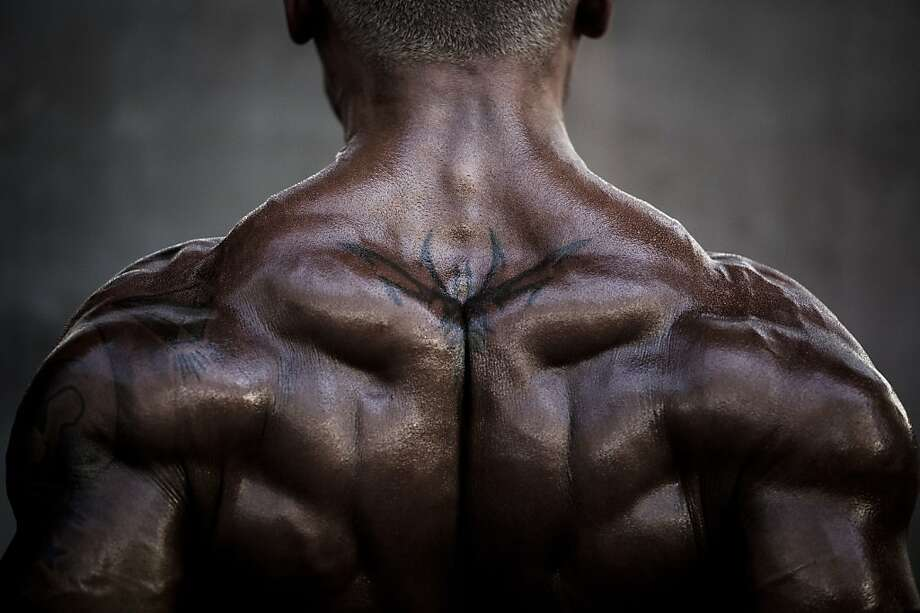 A competitor exercises as he waits backstage during the 2012 International Bodybuilding and Fitness Invitation Championship in Hong Kong on July 14, 2012.  Participants, who darken their skin with tanning products and apply oils to increase shine, do a series of mandatory poses and display their best shaped muscles to a panel of judges who assign points based on their appearance.    AFP PHOTO / Philippe LopezPHILIPPE LOPEZ/AFP/GettyImages Photo: Philippe Lopez, AFP/Getty Images