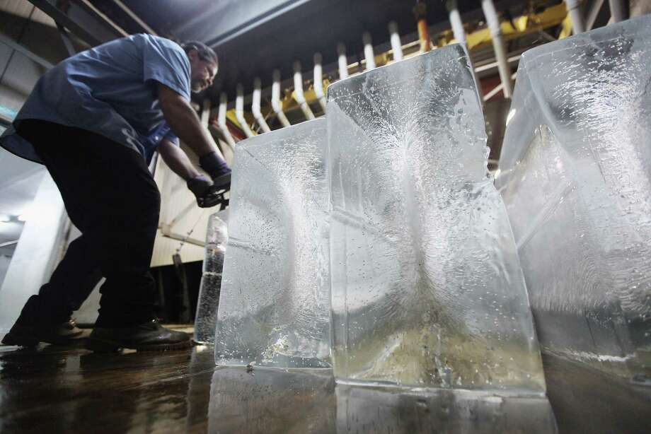 "NEW YORK, NY - JULY 17:  Ricky Perez unloads 300-pound blocks of ice from a brine tank to be sold at Arctic Glacier Premium Ice on July 17, 2012 in the Bronx borough of New York City. Perez said, ""Right now we are selling these things like crazy."" The blocks take three days to freeze in the tank and sell for $75. A heat advisory was issued in the city again today as high temperatures were expected in the 90's though tomorrow. Photo: Mario Tama, Getty Images / 2012 Getty Images"