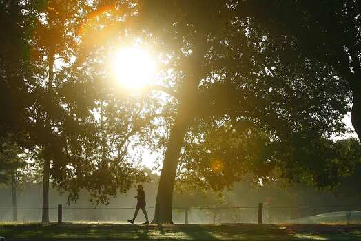 Morning sun shines through a misty morning as walkers meander through Hermann Park, on Wednesday, July 18, 2012. (Nick de la Torre /  Houston Chronicle ) Photo: Nick De La Torre / Houston Chronicle