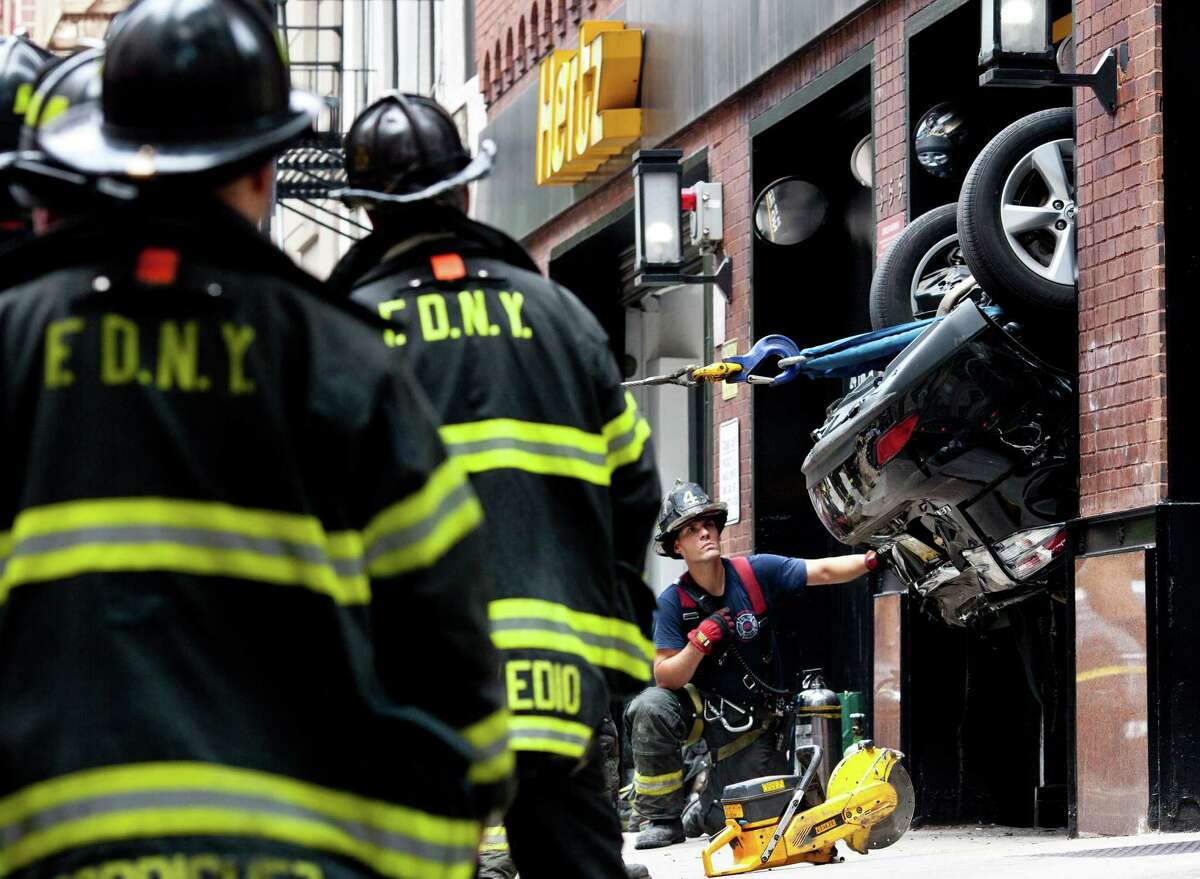 New York firefighters work to free a Lexus RX350 that fell into a parking garage elevator shaft in the Manhattan borough of New York, July 17, 2012. Two people were taken to an area hospital with non-life threatening injuries. (Brad Vest/The New York Times)